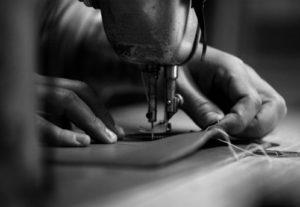 Sweden, Stockholm, Close up of sewing maschine and man's hands holding fabric